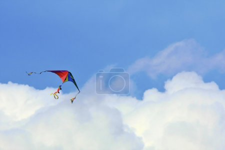 Rainbow colored kite in the clouds