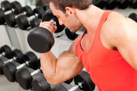 Photo pour Homme avec materiel de musculation sur club de sport gym - image libre de droit
