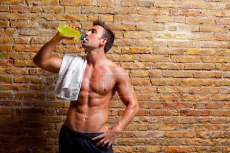 Photo for Muscle shaped man at gym relaxed drinking energy drink - Royalty Free Image