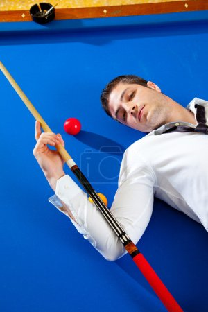 Billiard young man player lying on pool blue table