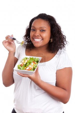 Photo for Young african american woman eating salad, isolated on white background - Royalty Free Image