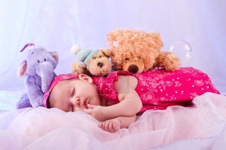 Photo for View of a newborn baby on smooth bed with stuffed toy sleeping. - Royalty Free Image