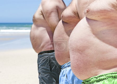 Close up of three obese fat men of the beach