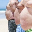 Close up of three obese fat men of the beach...