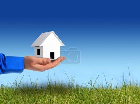 Photo pour Investir dans l'immobilier. main avec maison sur fond de ciel. - image libre de droit