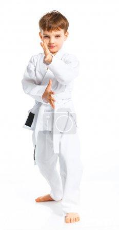 Photo pour Garçon d'Aïkido combats position en kimono blanc isolé sur blanc - image libre de droit