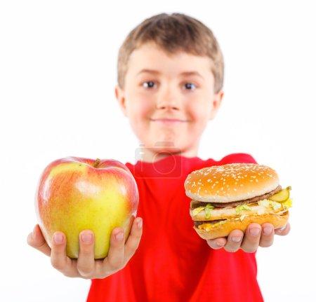 Photo pour Mignon garçon, manger une pomme ou un hamburger. mettre l'accent sur la pomme et le hamburger. isolé sur fond blanc - image libre de droit