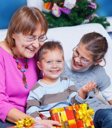 Photo pour Mignonne grand-mère et ses deux petits-enfants, je regarde les cadeaux de Noël - image libre de droit