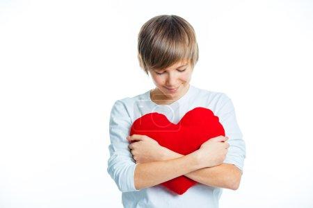 Photo pour Un mignon jeune garçon dans l'amour avec un coeur rouge en peluche dans les mains. isolé - image libre de droit