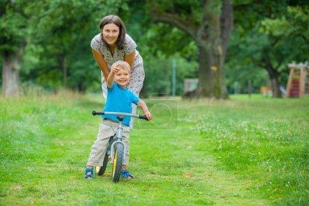 Photo pour Portrait du petit garçon sur une bicyclette et sa mère dans le parc de l'été - image libre de droit