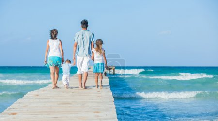Photo for Family of four on wooden jetty by the ocean. Back view - Royalty Free Image