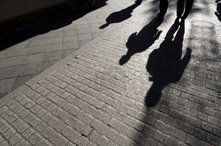 Shadows of walking along a cobblestone street, Sev...
