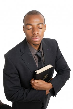 Business man on his knees holding a bible