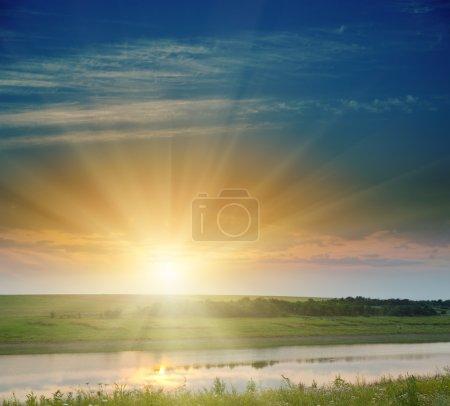 Photo pour Bon coucher de soleil sur le champ et la rivière - image libre de droit