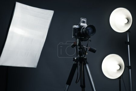 Photo pour Fond studio avec accessoires de lumière, grand appareil photo vintage (6x6), trépied, softbox, stands - image libre de droit