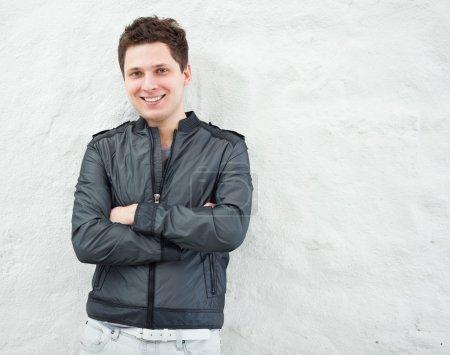 Photo pour Jeune homme beau en vêtements décontractés appuyé contre le mur - image libre de droit