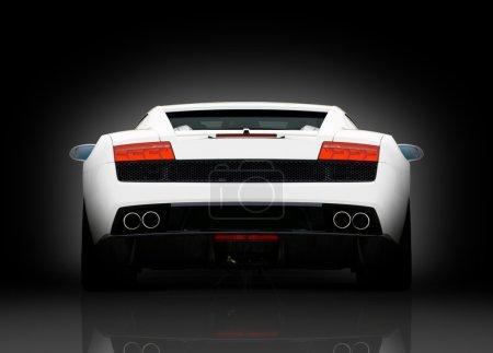 Photo pour Vue arrière de supercar blanc sur fond noir avec réflexion dans le sol - image libre de droit