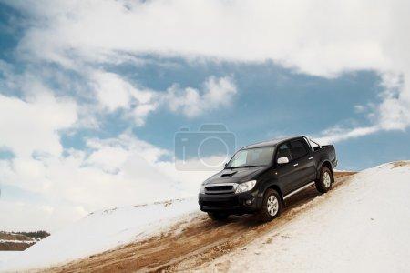 Photo pour Noir camionnette conduite vers le bas de la colline sur une route de sable - image libre de droit