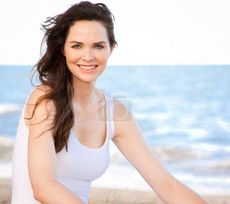 Photo pour Portrait d'une belle jeune femme en bonne santé assise sur la plage - image libre de droit