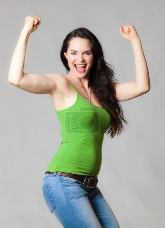 Photo pour Une heureuse jeune femme en forme gaie fléchissant ses muscles - image libre de droit