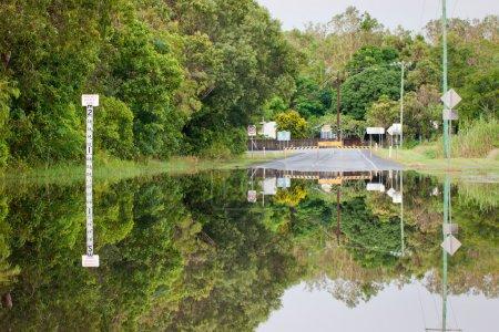 Photo pour Une route inondée avec des indicateurs de profondeur et de belles réflexions - image libre de droit