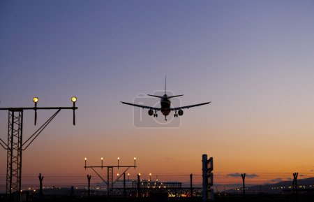 Photo for Plane landing on the runway at dusk - Royalty Free Image