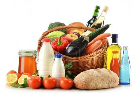 Photo pour Composition avec des aliments crus, y compris les légumes, les fruits, le pain et le vin présentés dans un panier en osier isolé sur blanc - image libre de droit