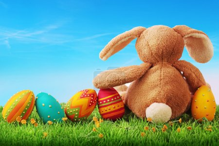 Photo for Colorful easter eggs and rabbit on green grass - Royalty Free Image