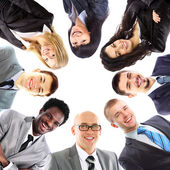 Group of business standing in huddle, smiling, low angle view