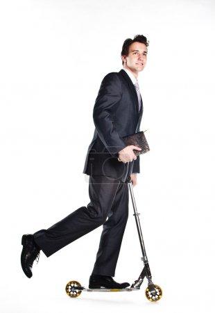 Photo pour Portrait d'un jeune homme respectable et prospère dans un costume d'affaires sombre qui chevauche un scooter - image libre de droit