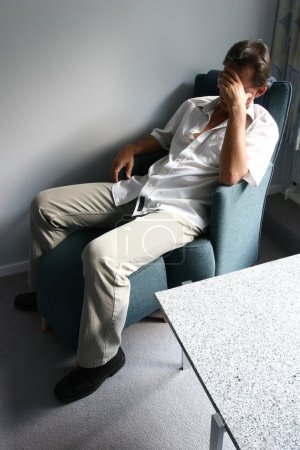 Photo for Desperate and tired man in a chair with hand on head - Royalty Free Image