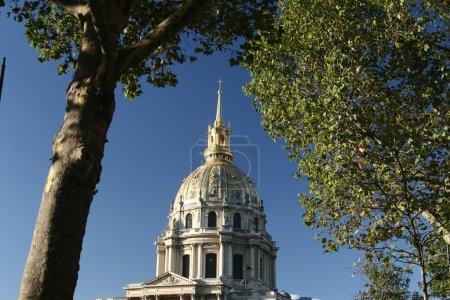 Photo pour L'immeuble invalide de Paris. Vue du toit entre deux arbres. L'invalide est le lieu de la tombe de Napoléon Bonaparte - image libre de droit