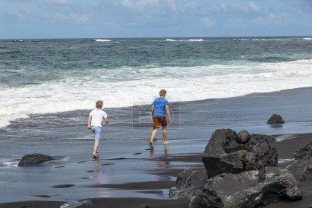 Boys have fun at the black volcanic beach