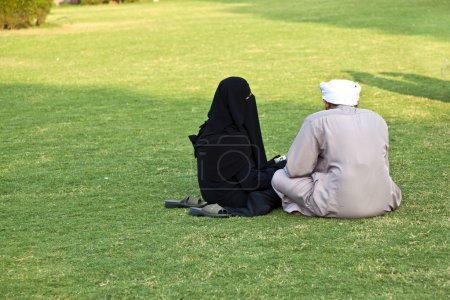 Islamic woman in burka sitting on the green with her husband