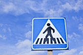 Pedestrian crossing sign with blue sky
