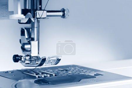 Foto de Primer plano del pie de máquina de coser moderna. imagen entonada azul, con espacio de copia. centrarse en la aguja - Imagen libre de derechos