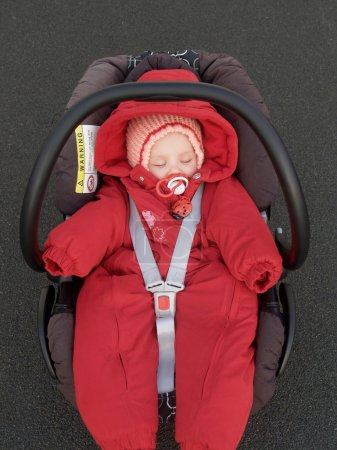 The baby sleeps in a children autosafety
