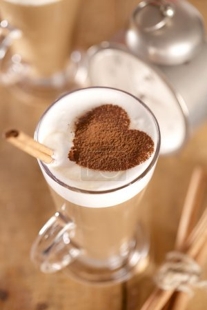 Coffee latte with cinnamon sticks and cacao heart , shallow dof