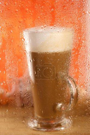 Coffee latte behind rainy window, shallow dof on glass with drop