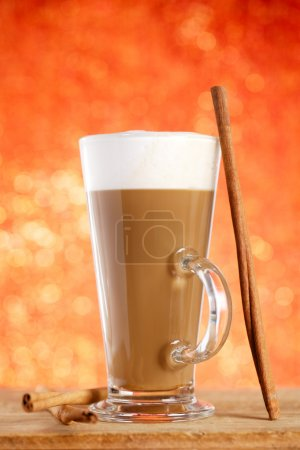 Coffee latte with cinnamon sticks, red glitter backdrop, shallow