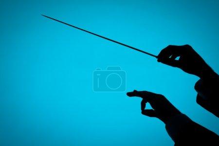 Photo pour Des mains de chef d'orchestre, une avec matraque. Silhouette sur fond bleu . - image libre de droit