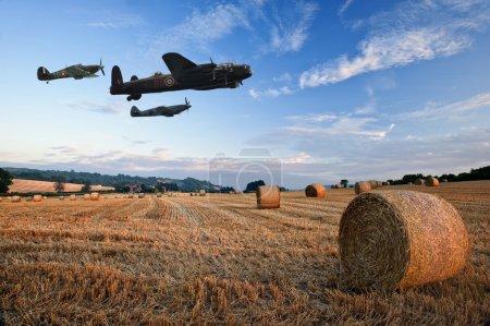 Photo pour La guerre mondiale 2 avions de raf survolant paysage magnifique coucher du soleil heure d'or de balles de foin en champ dans la campagne anglais - image libre de droit