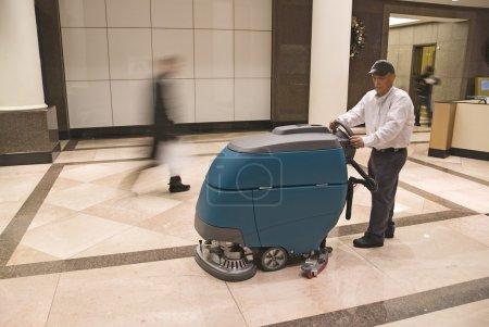 Foto de Operador de máquina limpieza de piso en edificio comercial lobby - Imagen libre de derechos