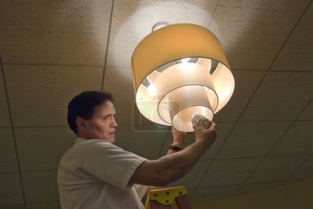 Photo for Maintenance man changing light bulbs in business office - Royalty Free Image