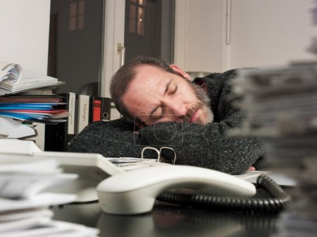 Photo for Mature businessman sleeping on papers at office-overworked at night time. Horizontal shot - Royalty Free Image