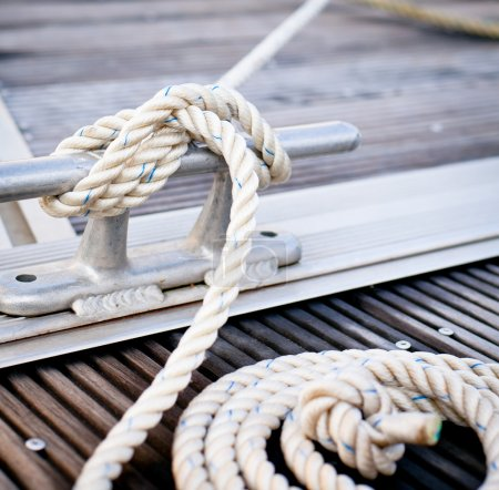 Photo for Close-up of a mooring rope with a knotted end tied around a cleat on a wooden pier. - Royalty Free Image