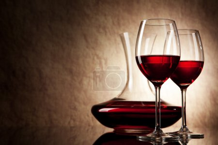 Photo for Decanter with red wine and glass on a old stone background - Royalty Free Image