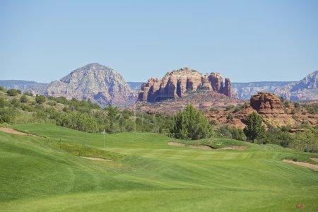 Photo pour Une toile de fond rocheuse rouge à un pittoresque trou de golf sedona arizona - image libre de droit