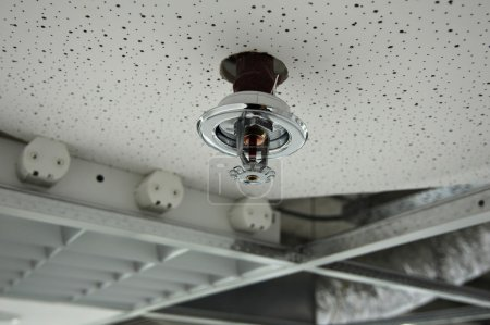 Photo for Installation process of a fire sprinkler in a ceiling - always ready for spraying water on a fire. Useful file for your brochure about security, safety and water piping systems. - Royalty Free Image