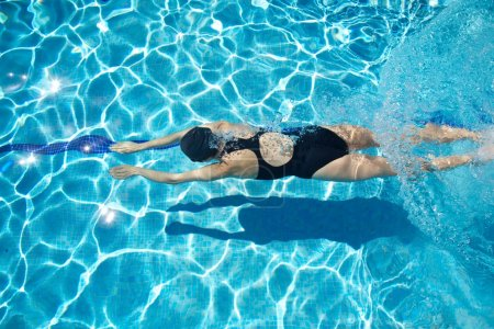 Photo for Woman with swimsuit swimming on a blue water pool - Royalty Free Image